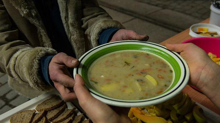 Geflüchtete kochen für Obdachlose