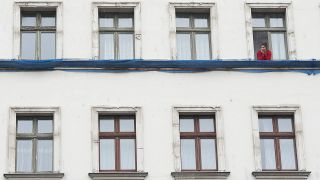 Frau am Fenster in Berlin (Quelle: imago-images/ Seeliger)