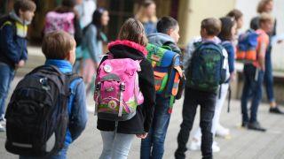 Symbolbild- Schülerinnen und Schüler der vierten Klasse stehen auf einem Schulhof mit Abstand zueinander in einer Reihe. (Bild: dpa/Arne Dedert)