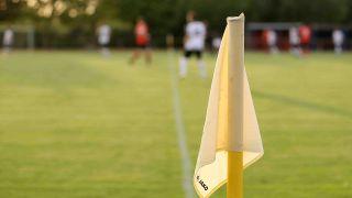 Eine Eckfahne beim Fußball, im Hintergrund läuft ein Spiel. Quelle: imago images/Claus Bergmann