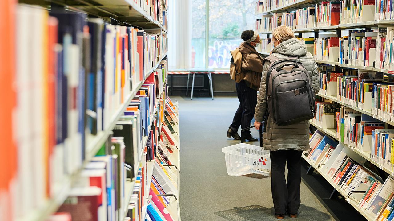 Zwei Besucherinnen stehen zwischen Bücherregalen in der Zentral- und Landesbibliothek Berlin