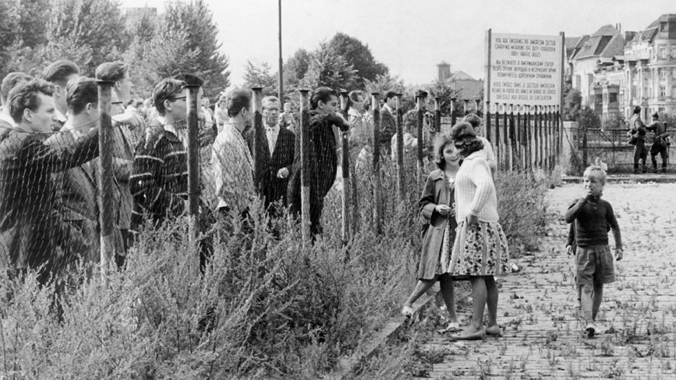 Mehrere Gruppen von Bürgern Westberlins schauen am 13.08.1961 in einer Straße in Berlin-Neukölln bei der Errichtung der Grenzmauer zu. (Quelle: dpa)