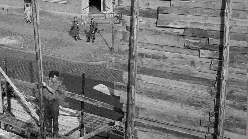 """Damit auch die Sicht über die neue Spermauer nicht mehr frei ist, errichtet die DDR-Regierung nun auch bis zu zehn Meter hohe Bretterwände als """"Sichtschutz"""". Unser Bild zeigt den Bau einer solchen Bretterwand am 12.10.1961 an der Schwedter/Ecke Gleimstraße, am sogenannten Gleimtunnel, in Berlin. Volkspolizisten beobachten die Arbeiten. (Quelle: dpa)"""