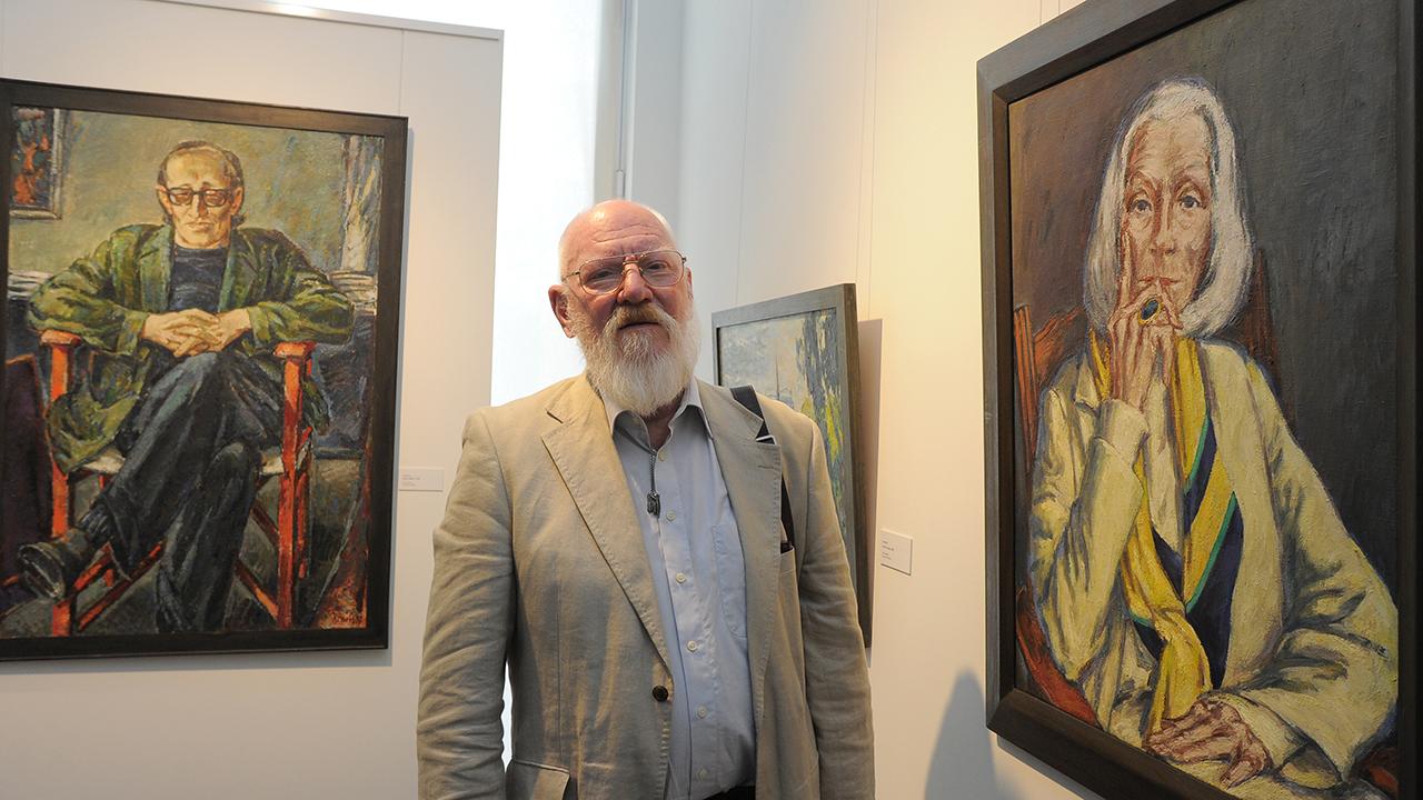 Der Maler Ronald Paris steht in Potsdam zwischen seinen Porträts von Heiner Müller und Inge Keller. (Quelle: dpa/Bernd Settnik)