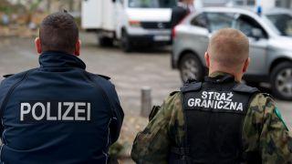 Ein polnischer Grenzpolizist (r) und ein deutscher Bundespolizist stehen nebeneinander am Rande der deutsch-polnischen Sicherheitstagung in Frankfurt (Oder) (Brandenburg). Quelle: Patrick Pleul/dpa