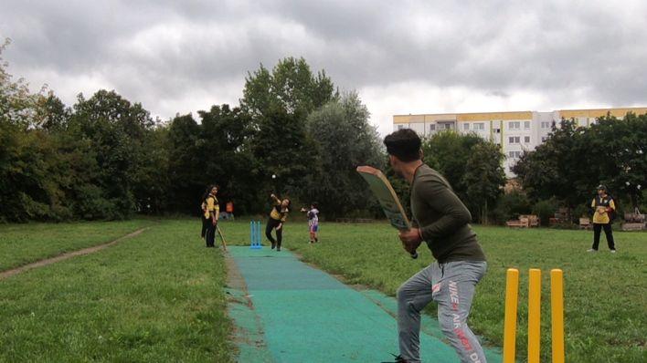 Cricket Training auf dem Platz in Hellersdorf. Vorne steht der Trainer mit dem Schläger, hinten wirft eine Spielerin. Bild: rbb
