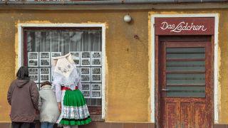 Frau in original sorbisch-wendischer Spreewaldtracht steht an Ladenfenster (Foto: dpa/Pleul)
